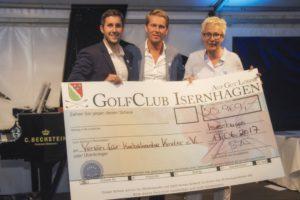 Christopher Bielke, Clubmanager des Golf Club Isernhagen, und Georgia Mysegades bei der Scheckübergabe. In der Mitte Moderator Hinnerk Baumgarten. Weitere Spenden kamen im Laufe des Abends hinzu.